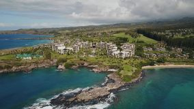 Fly over the pacific ocean with comfortable resort montage kapalua and picturesque terrain on islands maui,hawaii stock video footage