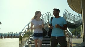 Two friends having pleasant conversation outdoors. Exciting talk. Two faithful friends discussing recent news with astonishment while going in city surrounding stock footage