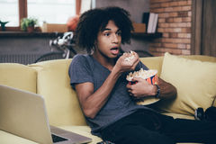 Exciting TV show. Young African man watching TV and keeping his mouth open while sitting with bucket of popcorn on the couch at home Stock Photo