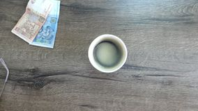 A cup of black coffee on a table and money paid for it. An exciting view of a cup of black coffee on a wooden table and money paid for it. One hand puts stock footage