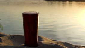 A plastic cup of coffee on a lake bank at a nice sunset in summer. An exciting view of a plastic cup of hot coffee on a picturesque lake bank at a splendid stock video footage