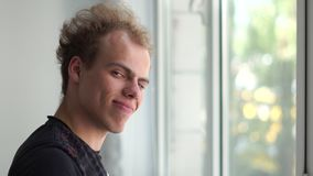Funny man looking out the window and looking aside with a smile in a studio in slo-mo. Exciting view of a young blond man with fluffy fair hair in a black T stock video footage