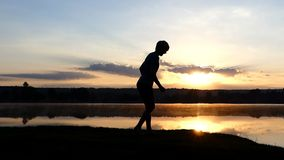 Young man does a moon walk of Michael Jackson at sunset