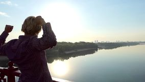Young Man Raises His Hands on a Bridge Over The Dnipro at Sunset in Slo-Mo. An Exciting View of a Young Man Who Stands, Looks Up, and Raises His Hands, on a stock footage