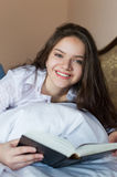 Exciting young female laying with open book on Royalty Free Stock Photo