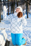 Exciting young woman with hands up standing on bench in winter park Stock Photos
