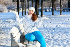 Exciting young woman with hands up at winter park. Exciting young Caucasian woman with hands up at winter park Royalty Free Stock Photos