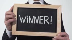 Exclamación del ganador escrita en la pizarra en manos del hombre de negocios, persona acertada metrajes