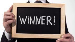 Exclamación del ganador escrita en la pizarra en manos del hombre de negocios, persona acertada foto de archivo