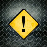 Exclamação Mark Grunge Yellow Warning Sign na cerca de Chainlink Fotos de Stock