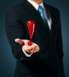 Exclamation mark. Man holds an exclamation mark in a hand stock images