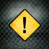 Exclamation Mark Grunge Yellow Warning Sign sur la barrière de Chainlink Photos stock