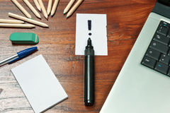 Exclamation mark over a black pen on writing desk Royalty Free Stock Image