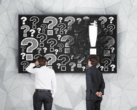 Exclamation and question mark. Two businessman looking at exclamation and question mark Stock Image