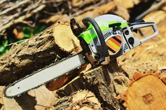 The excluded chainsaw lies on a stump. Near a large fresh log royalty free stock images
