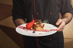Exclusief dessert in chef-kokhanden op witte plaat, close-up stock foto