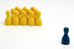 Exclusion. Group of yellow counters with a blue counter off to one side, isolated on a white background. Narrow depth of field Royalty Free Stock Image