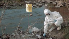 Exclusion zone in nature, hazmat virologist into Protective clothing taking infected water sample in test tubes for