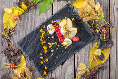 Exclusive autumn cream dessert with pears, currants and pistachios on black board, decorated with flowers petals, product photogra Stock Photo