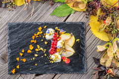 Exclusive autumn cream dessert with pears, currants and pistachios on black board, decorated with flowers petals, product photogra Stock Photography