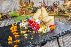 Exclusive autumn cream dessert with pears, currants and pistachios on black board, decorated with flowers petals, product photogra Royalty Free Stock Images
