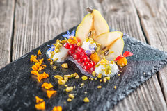 Exclusive autumn cream dessert with pears, currants and pistachios on black board, decorated with flowers petals, product photogra Stock Image