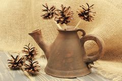 Exclusive clay teapot of unusual shape with decorative flowers from open pine cones on the background of coarse jute fabric. Black. Ceramic teapot of unusual stock photos