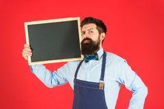 Exclusive cocktail. Hipster restaurant staff. Hipster informing you. Man bearded bartender or cook in apron hold blank. Chalkboard. Price list concept. Hipster royalty free stock photography