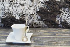 Coffee porcelain cup and saucer of white color and silver spoon with twisted handle against background of birch bark. Rough old stock image