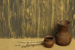 Exclusive earthenware jugs and birch twigs on rough burlap against the background of old wooden boards royalty free stock image