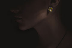Exclusive jewelry accessories concept. dark picture with bright earring on woman. luxury. Royalty Free Stock Photography