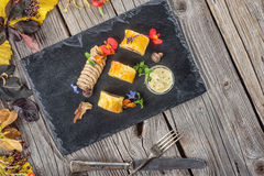 Exclusive puff pastry appetizer with meat pie decorated with mushrooms and herbs on black board with autumn leaves and cutlery, pr. Oduct photography for stock photo