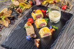 Exclusive puff pastry appetizer with meat pie decorated with mushrooms and herbs on black board with autumn leaves and sauce, prod. Uct photography for royalty free stock photo