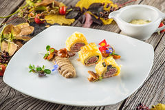 Exclusive puff pastry appetizer with meat pie decorated with mushrooms and herbs on white plate with autumn leaves and sauce, prod. Uct photography for stock photo