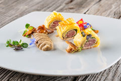 Exclusive puff pastry appetizer with meat pie decorated with mushrooms and herbs on white plate, product photography for. Restaurant stock photo