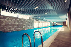 Exclusive swimming pool in a wellness hotel.Luxury resort indoor swimming pool with beautiful clean blue water Royalty Free Stock Photo