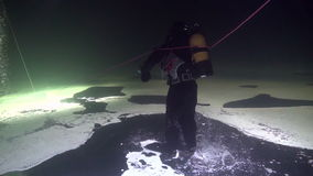 Exclusive trick diver underwater in ice of White Sea. Exclusive trick diver underwter in ice of White Sea. Creative diving and dangerous extreme sport. Unique stock video footage