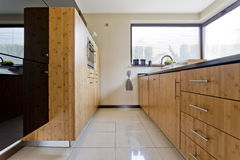 Exclusive wooden kitchen. Narrow exclusive wooden kitchen idea in contemporary house stock images
