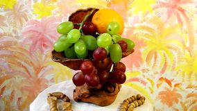 Exclusive wooden vase with  grapes and oranges Stock Photo