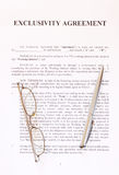 Exclusivity agreement form with pen and glasses. Exclusivity agreement with pen and glasses royalty free stock photos