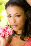 Exotic woman. Beautiful exotic woman with a red hibiscus Royalty Free Stock Photos