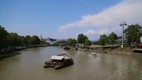 Excursão da água no Rio Kura em Tbilisi, Geórgia, ponte da paz no fundo vídeos de arquivo