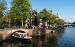 Excursion boat in Amsterdam canal Stock Photo