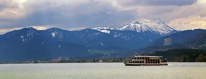Excursion boat in the lake tegernsee with blue and snow covered. Mountains in the background, panoramic view on the famous tourist resort in the Bavarian Alps Royalty Free Stock Image