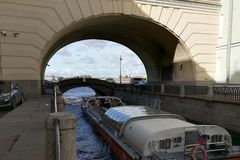 Excursion boat passes through the arch of the bridge in the historical center of Saint-Petersburg. The excursion boat passes through the double arch of the stock photos