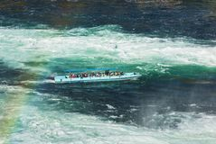 Excursion boat at the Rhine Falls in Switzerland. Laufen, Switzerland - 17 October, 2017: an excursion boat on the Rhine river just below the Rhine Falls Royalty Free Stock Images
