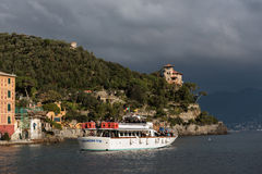 Excursion boat at the stormy bay of Portofino town, Italy Royalty Free Stock Photos