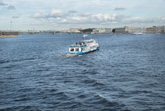 Excursion boat with tourists floats on the Neva river in St. Petersburg, Russia. Royalty Free Stock Photography