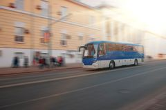 Excursion city bus moves along large city street. Motion blur. Sunny day Royalty Free Stock Photo