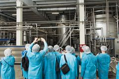 Excursion at the factory. People in protection, shoe covers, blue overalls stand and listen to a tour of the metal brewery. People